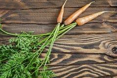 Świeże organicznie marchewki z wierzchołkami na drewnianym stole zdjęcia royalty free