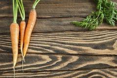 Świeże organicznie marchewki z wierzchołkami na drewnianym stole zdjęcia stock