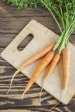 Świeże organicznie marchewki z wierzchołkami na tnącej desce Zdjęcia Stock