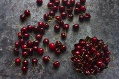 Świeże organicznie wiśnie w metalu pucharze na zmroku drylują tło Fotografia Royalty Free