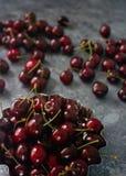 Świeże organicznie wiśnie w metalu pucharze na zmroku drylują tło Zdjęcie Stock