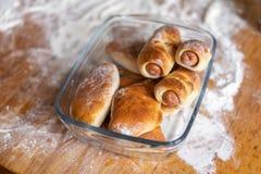 Świeże piec babeczki z kiełbasą i kulebiakami kłamają w szklanym talerzu na drewnianym stole zakrywającym z mąką zdjęcie royalty free