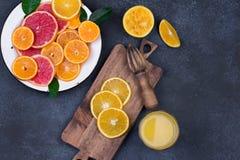 Świeże pomarańcze, grapefruits i madarine plasterki na zmroku, drylują tło zdjęcie stock