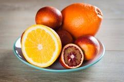 Świeże pomarańczowe i krwionośne pomarańcze matrycować w drewnianej powierzchni zdjęcia stock