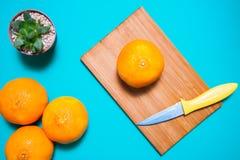 Świeże pomarańczowe owoc i sok na błękitnym tło stole fotografia stock