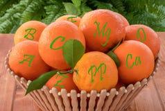 Świeże pomarańczowe owoc w drewnianym pucharze z vitaminand kopalnymi imionami zdjęcie stock