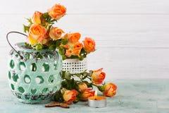 Świeże pomarańczowe róże kwitną w nowej wazie i zaświecającej świeczce Fotografia Stock