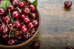 Świeże słodkie wiśnie rzucają kulą z liśćmi na drewnianym stole fotografia stock