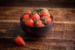 Świeże smakowite truskawki w czarnej filiżance na drewnianym stole Truskawka na stole obok filiżanki jagoda Zdjęcia Royalty Free