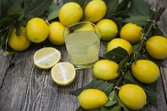 Świeże soczyste cytryny i szkło domowej roboty lemoniada na drewnianym tle Fotografia Stock