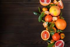 Świeże soczyste owocowe pomarańcze, tangerines, persimmon, grapefruitowy na białym talerzu w rżniętym zbliżeniu na zmroku texture fotografia royalty free