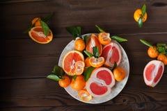 Świeże soczyste owocowe pomarańcze, tangerines, persimmon, grapefruitowy na białym talerzu w rżniętym zbliżeniu na zmroku texture zdjęcia stock