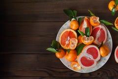 Świeże soczyste owocowe pomarańcze, tangerines, persimmon, grapefruitowy na białym talerzu w rżniętym zbliżeniu na zmroku texture fotografia stock