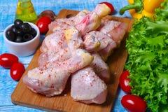 Świeże surowe kurczak nogi na tnącej desce z warzywami i pikantność na drewnianym tle Zdjęcie Stock
