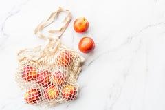 ?wie?e surowe nektaryny k?ama w smyczkowej torbie na bielu wyk?adaj? marmurem t?o Mieszkanie nieatutowy, odg?rnego widoku lato, ? obrazy stock