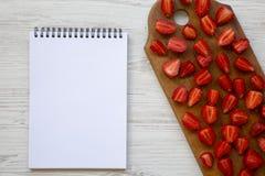 Świeże truskawki na drewnianej deski i pustego miejsca notepad, odgórny widok kosmos kopii Biały Drewniany stół Od above, Obrazy Royalty Free