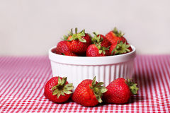 Świeże truskawki w Białym pucharze na Czerwonym Gingham Tablecloth obraz royalty free