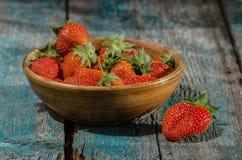 Świeże truskawki w glinianym garnku na starej drewnianej desce Fotografia Stock
