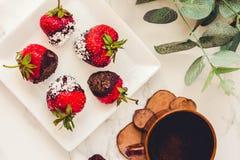 Świeże truskawki zamaczali w ciemnych czekoladowych i kokosowych płatkach w Obrazy Stock
