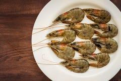 Świeże uncooked królewiątko krewetki w białym talerzu na brązu drewnianym tle Delikatności, smakowitego i zdrowego denny jedzenie fotografia royalty free