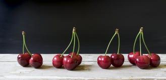 Świeże wiśnie na drewnianym stole z czarnym tłem Zdjęcie Stock