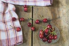 Świeże wiśnie na starym, nieociosanym drewnianym tle, Fotografia Stock
