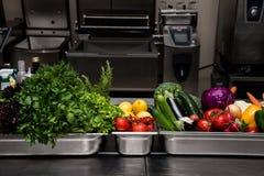 Świeże zielenie w metalu rzucają kulą na fachowej kuchni Selekcyjny fo Zdjęcie Stock