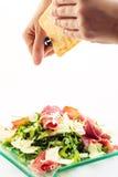 Świeżego arugula jarzynowa sałatka z baleronem i serem na szklanym talerzu na białych kucharzach i tle wręcza strzępienie ser, pr obraz stock