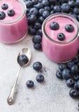 Świeżego hommemade czarnej jagody śmietankowy jogurt z świeżymi czarnymi jagodami i srebną łyżką na kamiennym kuchennego obraz royalty free