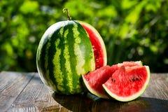 Świeżego pokrojonego arbuza drewniany tło, Dojrzały pasiasty watermelo obraz royalty free