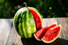 Świeżego pokrojonego arbuza drewniany tło, Dojrzały pasiasty watermelo fotografia stock