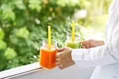 Świeżego smoothie detox jarzynowa marchwiana sałata i ogórek w ręce na natury tle Zdjęcia Stock