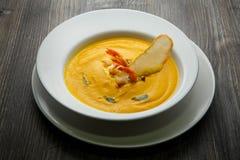 Świeżej kolor żółty ryby kremowa polewka z krewetka ogonami i jeden plasterkiem wysuszony chleb obraz royalty free