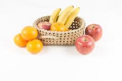Świeżej owoc bananowa jabłczana pomarańcze w koszykowym onwhite tle Zdjęcia Royalty Free