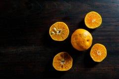 Świeżej połówki rżnięte pomarańcze na ciemnym drewnianym stole Zdjęcie Royalty Free