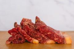 Świeżej surowej wołowiny stku mięśni plasterki na drewnianym cięciu wsiadają nad białym tłem fotografia stock