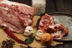 Świeżej wieprzowiny surowy mięso na papierze z pikantność na ciemnym drewnianym stole Kawałek wieprzowiny mięsa zakończenie Mięso Zdjęcia Royalty Free