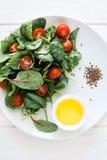Świeżej wiosny jarska sałatka z sałaty mieszanki, czereśniowych pomidorów, oliwa z oliwek i lna ziarnami, Zdjęcia Stock