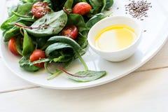 Świeżej wiosny jarska sałatka z sałaty mieszanki, czereśniowych pomidorów, oliwa z oliwek i lna ziarnami, Zdjęcia Royalty Free