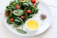 Świeżej wiosny jarska sałatka z sałaty mieszanki, czereśniowych pomidorów, oliwa z oliwek i lna ziarnami, Fotografia Stock