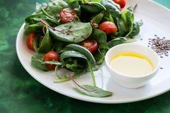 Świeżej wiosny jarska sałatka z sałaty mieszanki, czereśniowych pomidorów, oliwa z oliwek i lna ziarnami, Zdjęcie Stock