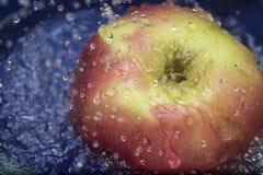Świeżej wody pluśnięcie na czerwonym jabłku obraz royalty free