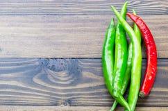 Świeżej zieleni i rewolucjonistki chili na drewnianym tle Zdjęcie Royalty Free