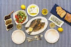 Świeżo gotować owoce morza piec na grillu dennego leszcza ryba, sardynki w oliwa z oliwek i warzywo sałatka, oliwki, feta ser, ch Obraz Royalty Free