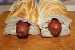 Świeżo gotujący hot dog w kolorowych chlebowych kijach na drewnianej powierzchni fotografia royalty free
