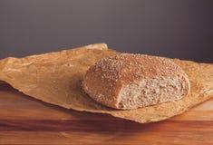 Świeżo piec bochenek wholemeal chleb z otręby na pieczenie papierze obraz stock