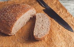 Świeżo piec bochenek wholemeal chleb z otręby na pieczenie papierze Pokrajać nożem obraz royalty free
