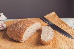 Świeżo piec bochenek wholemeal chleb z otręby na pieczenie papierze Pokrajać nożem fotografia stock