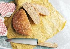 Świeżo piec bochenek wholemeal chleb z otręby na pieczenie papierze Pokrajać nożem fotografia royalty free