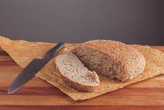 Świeżo piec bochenek wholemeal chleb z otręby na pieczenie papierze Pokrajać nożem zdjęcia stock